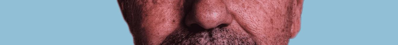 Visage nez d'homme de plus de 50 ans sur fond bleu