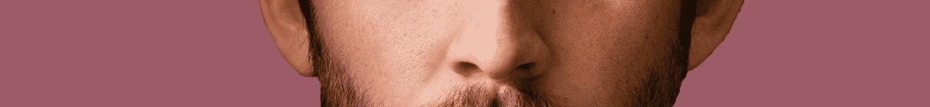 Visage nez jeune homme brun sur fond prune